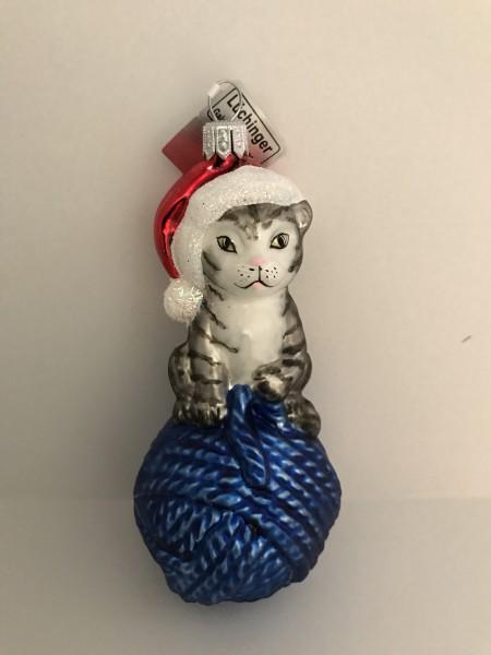 Graue Tiger-Katze sitzt auf blauem Wollknäuel