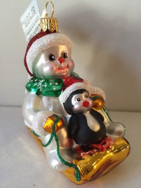 Schneemann mit Pinguin auf Schlitten