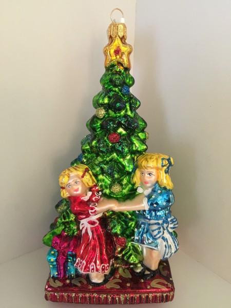 Zwei Mädchen tanzen um den Christbaum