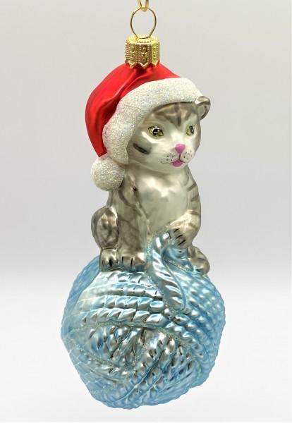 Graue Tiger-Katze sitzt auf hellblauem Wollknäuel