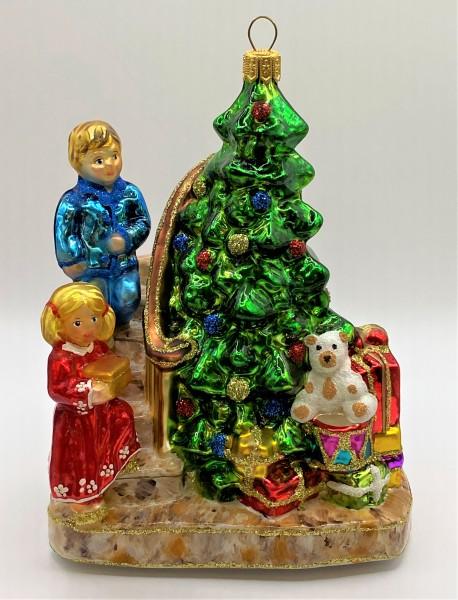 Die Kinder legen die Geschenke unter den Christbaum
